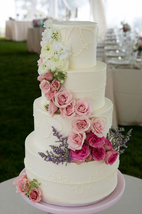Four-tiered white cake adorned with a cascade of roses and ranunculi