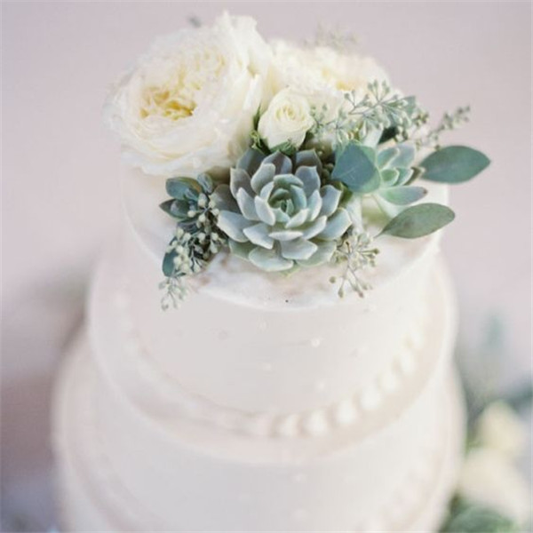 Traditional wedding cake topped with succulents and fresh flowers