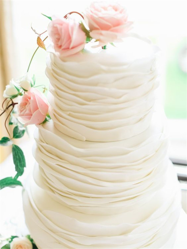 three tier white wedding cake decorated with fresh pink roses
