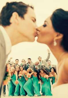 Cute shot of bride and groom kissing with wedding party behind them