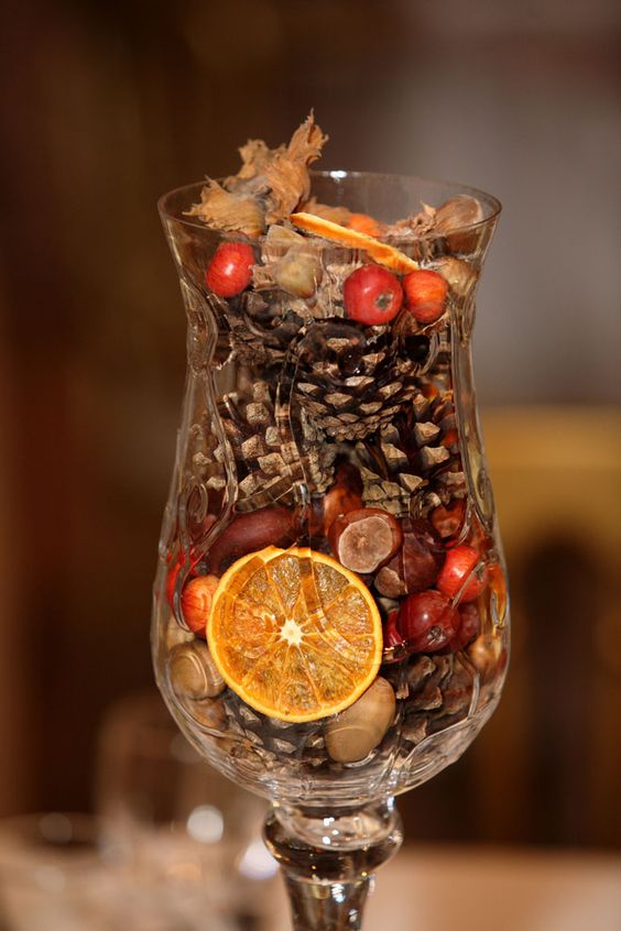 Fall wedding centrepieces - festive array of seasonal autumnal offerings like pinecones hazel nuts and colourful segments of dried oranges and rosehips