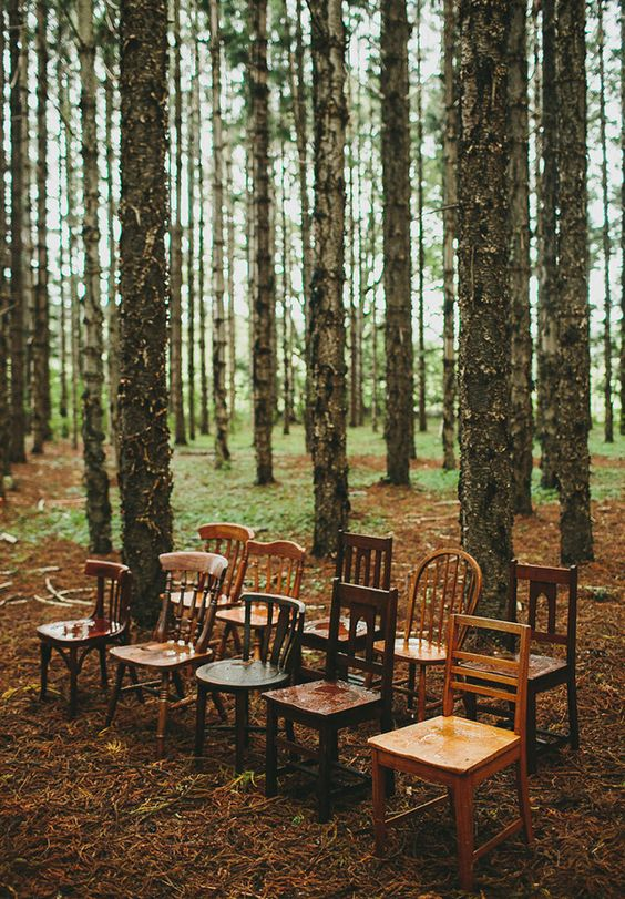This vintage setup is beautiful using simple missmatched chairs in a woodland wedding setting