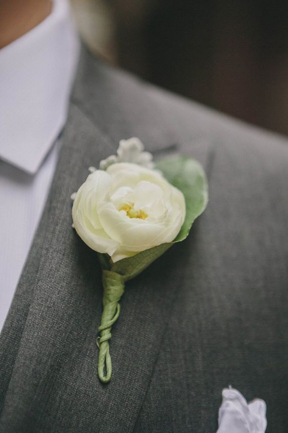White ranunculus boutonniere for the groom
