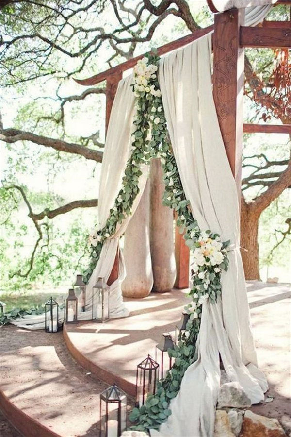 Woodland Wedding Arch with Billowy Fabric and a Cascade of Greenery