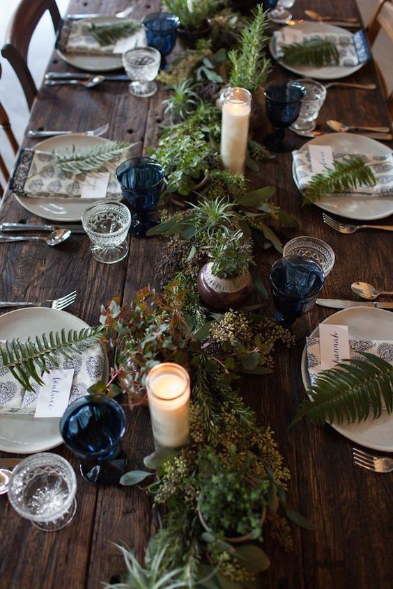 a rustic table is paired beautifully with earthy elements like ferns, berries and deep blue accents