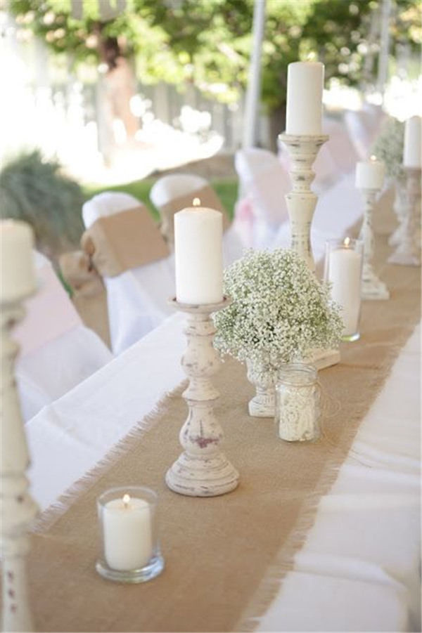 burlap runner over a simple white table cloths and rustic candle holder centerpieces