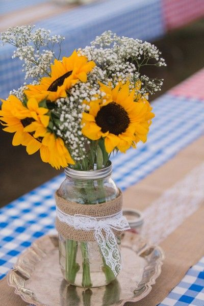 23 bright sunflower wedding decoration ideas for your rustic wedding a picnic themed reception table setting with burlap runners and mason jar centerpieces with a rustic wedding junglespirit Image collections