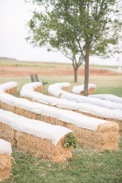 Hay bale seating at the rustic outdoor wedding ceremony
