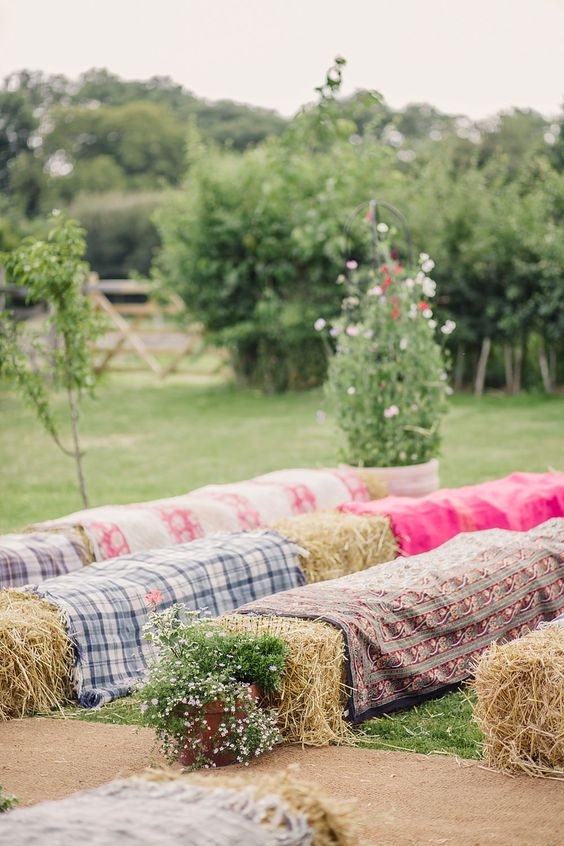 Hay bales as seating for the outdoor wedding ceremony in an English Country Garden