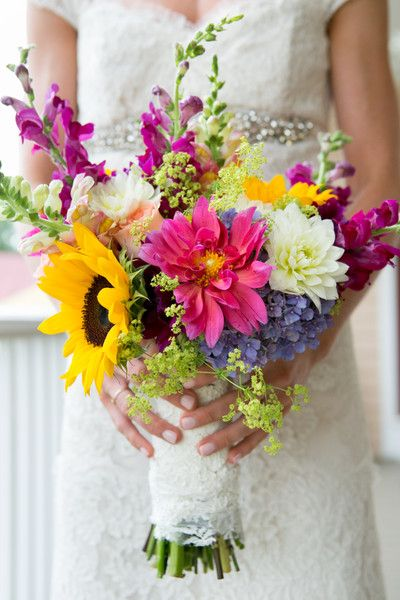 Wildflower bouquet of sunflowers, dahlias, roses, and craspedia balls.