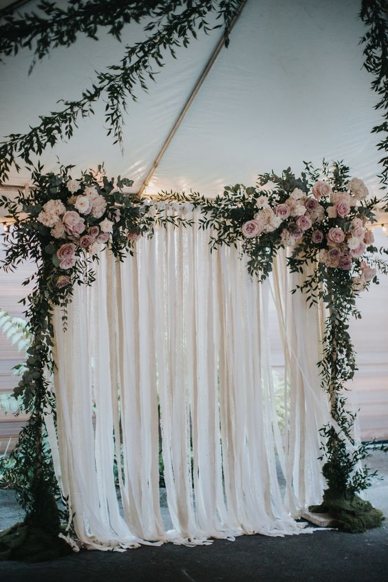 greenery arch with blush flowers and ribbon backdrop