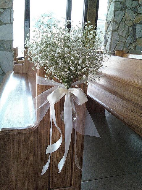like the idea of flowers and tying them to the pews