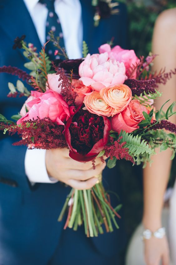 navy blue suite and dramatic bouquet of peonies and ranunculus roses