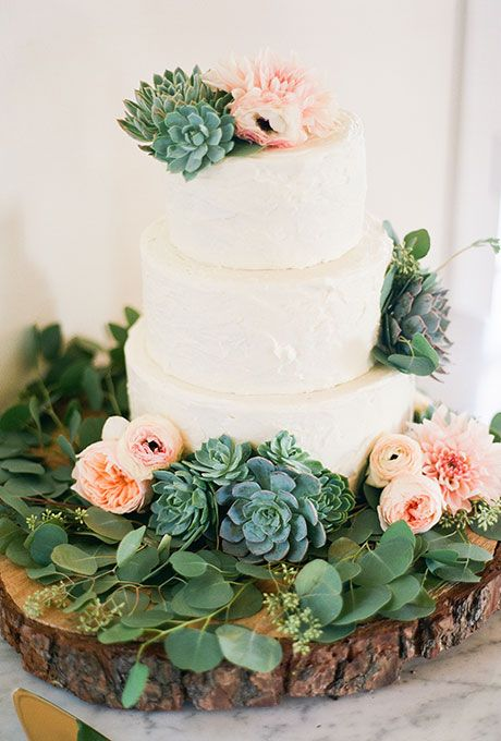 A three-tiered white wedding cake decorated with greenery and succulents