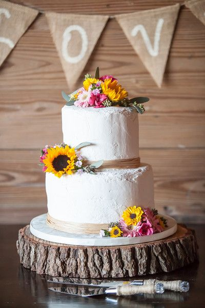 A two-tier buttercream wedding cake decorated with raffia ribbon and rustic blooms and displayed atop a tree slice