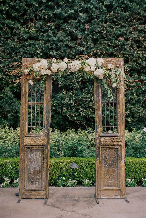 Old wooden doors with florals for a vintage ceremony backdrop