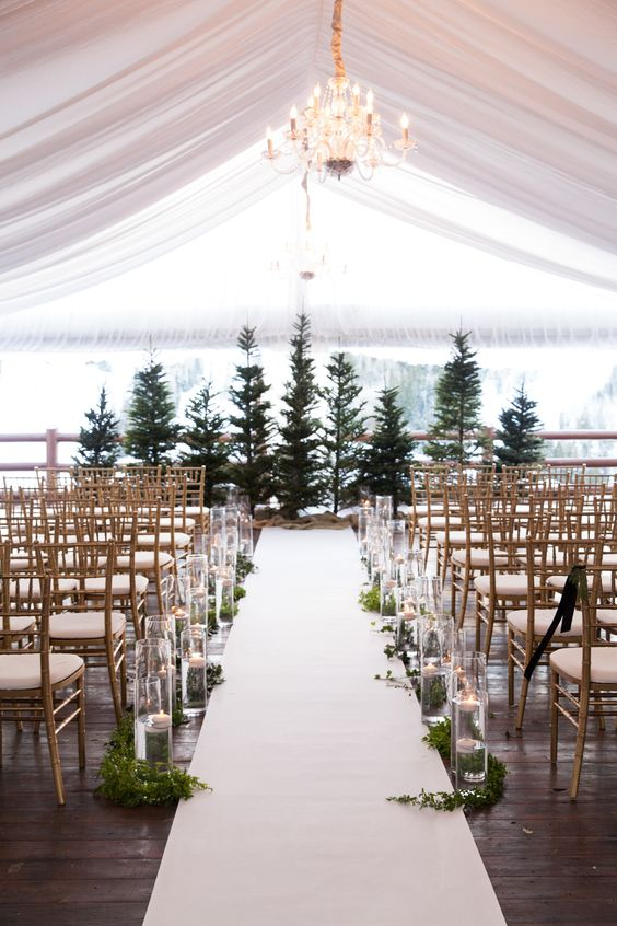 Tented wedding ceremony with evergreen trees and candles