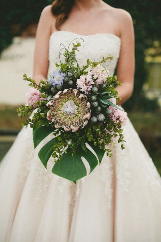 Wedding bouquet featuring king protea and monstera leaf