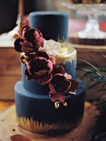 bold and dramatic wedding cake idea with metallic gold and berry colored flowers