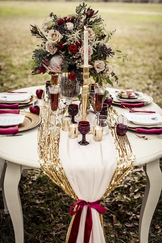 fall wedding table setting with a gold table runner and burgundy glasses