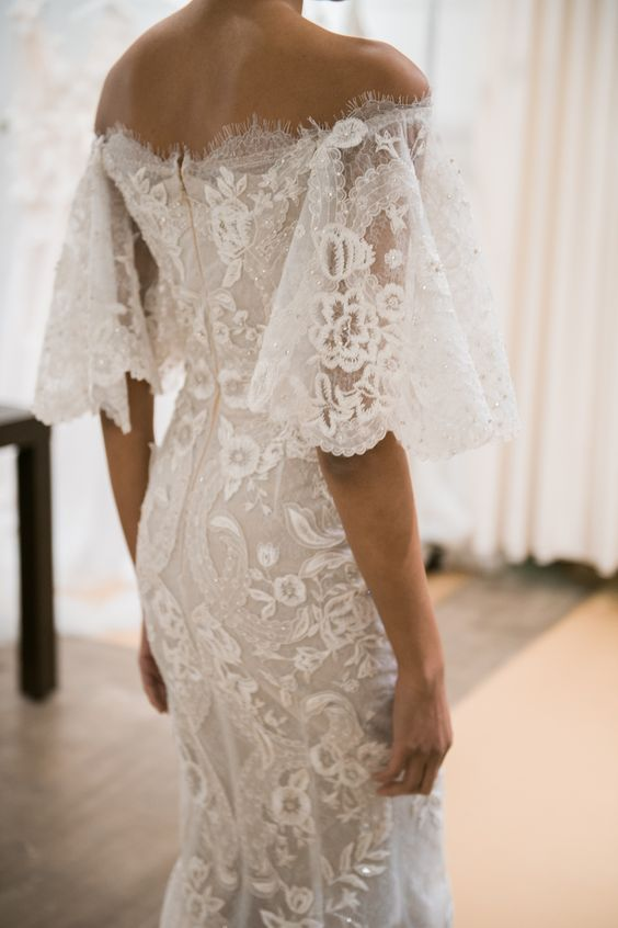 a boho lace wedding dress with a high neckline, lace bell sleeves, illusion sides and a cutout back