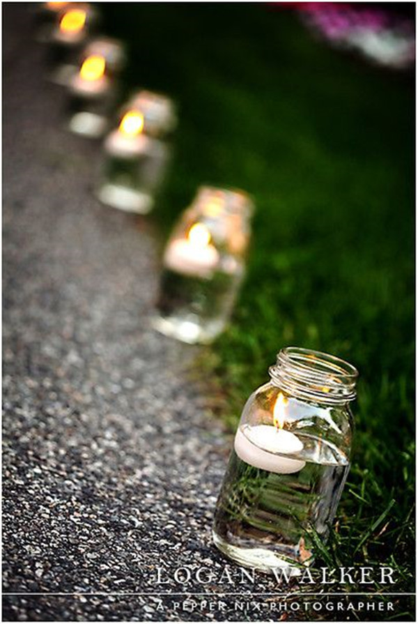 Mason jars with floating candles line the pathway to the backyard reception