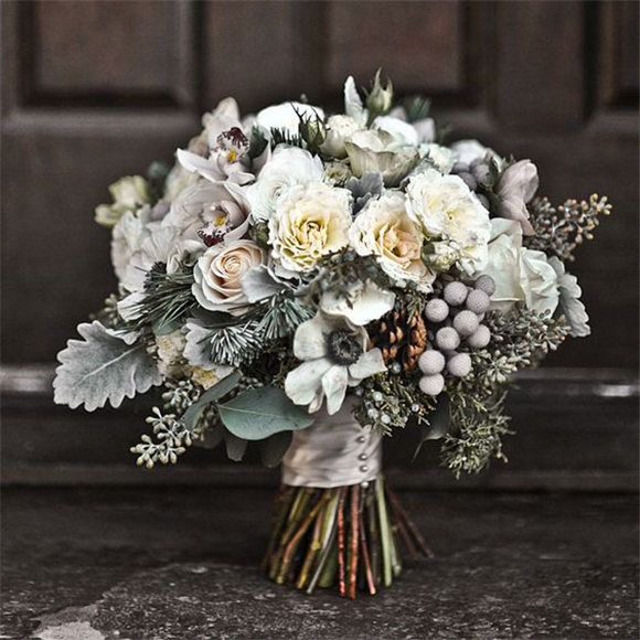 Winter wedding bouquet of mini cymbidium orchids, silver brunia, juniper, pine boughs, anemones, pine cones, garden spray roses