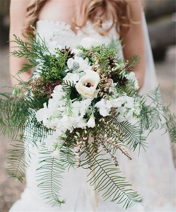 A rustic wedding bouquet with ferns, pieris, pinecones, and evergreens