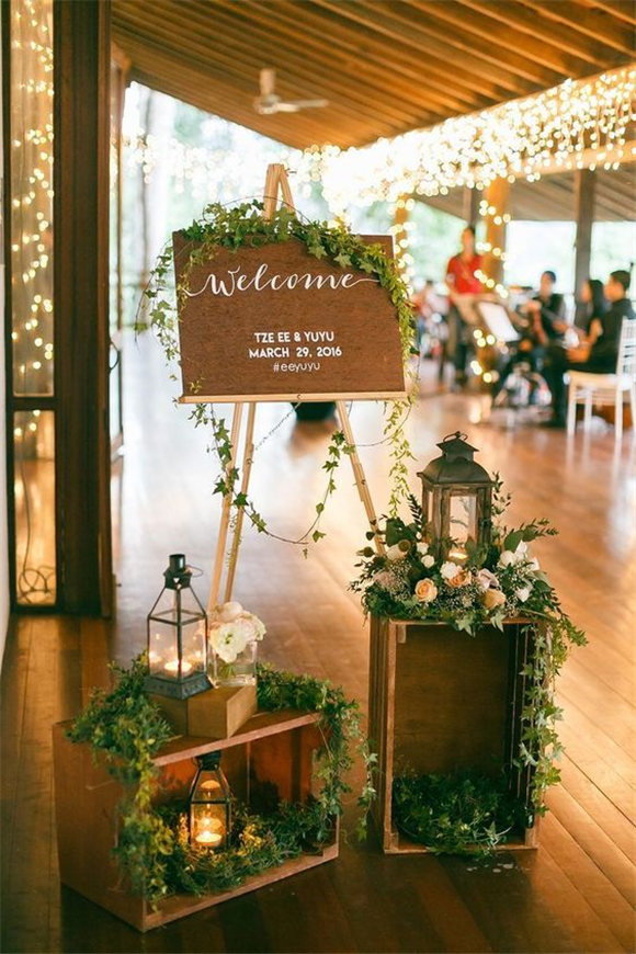 Dreamy wedding welcome sign with greenery and white Christmas lights