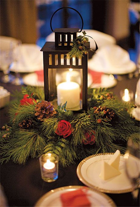 Wedding centerpiece of lanterns, pine boughs, roses, and pinecones